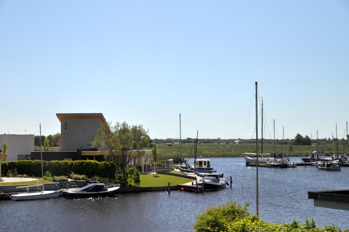 Uitzicht vanuit de slaapkamer over het water bij vakantiehuis aan de friese meren in Koudum